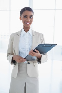 Cheerful elegant businesswoman in bright office holding clipboard