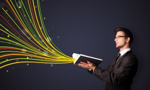 Young man reading a book while colorful lines are coming out of the book
