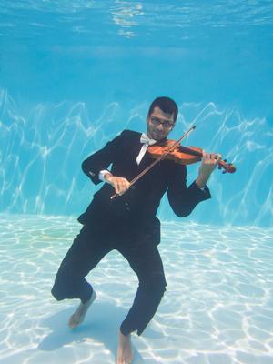 Aquatic music underwater violinist in suit